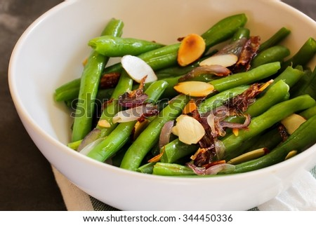 Green beans with almonds in a bowl close up, selective focus