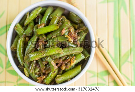 Green beans with garlic, onion and red pepper. Warm salad. The garnish ...