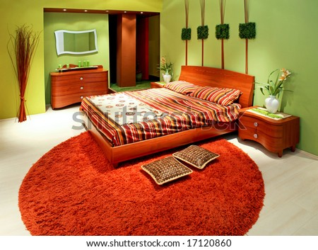 Green bedroom with big wooden double bed - stock photo