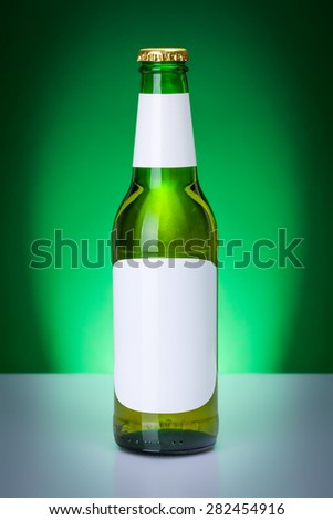 Green beer bottle with blank labels on elegant, backlit background