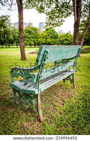 Green bench, chair, stool beside walkway in the public park, - stock photo