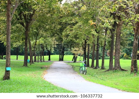 Green bench in peaceful park in Bangkok - stock photo