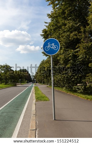 Green bicycle lane with a blue sign