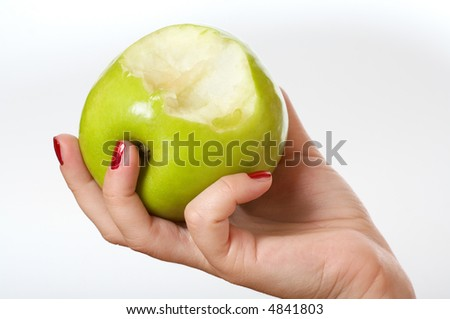 Green bitten apple in hand isolated on white background. - stock photo
