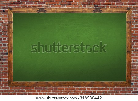 Green blackboard in wooden frame with eraser and chalk on brick wall - stock photo