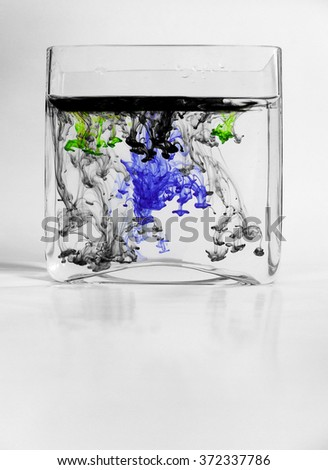Green, blue and black ink drops in glass vase with water - stock photo