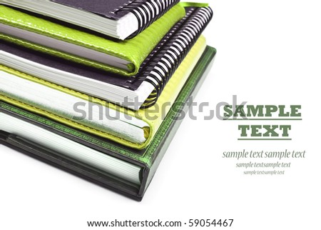 Green books stacked up - close up on a white background with space for text - stock photo