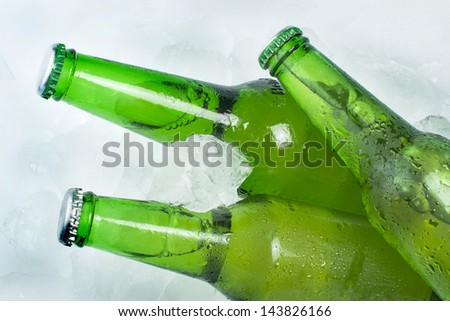 Green Bottle of beer and ice cubes - stock photo