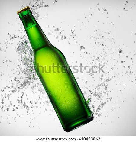 Green bottle of beer falling into water on white background - stock photo