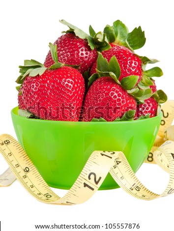 Green bowl of strawberries with a yellow measuring tape in front of it