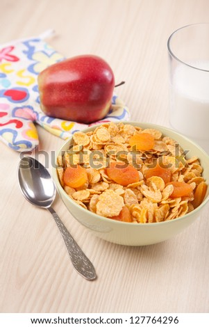 green bowls of crunchy corn flakes for breakfast with apple on wooden table
