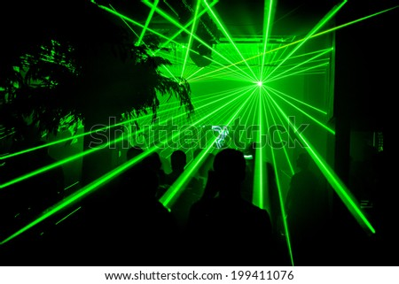 Green bright lasers at nightclub party rave - stock photo