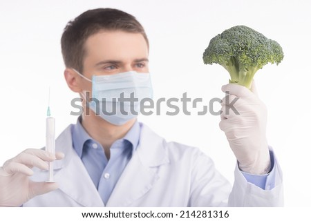 green broccoli in genetic engineering laboratory. man holding broccoli and needle on white background - stock photo