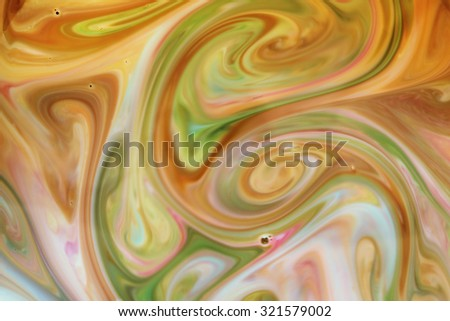 Green, brown and yellow jet watercolor in milk abstract background. - stock photo