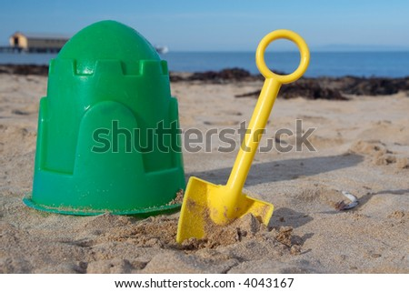 Green bucket and yellow plastic spade on the beach. - stock photo