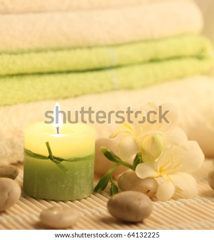 green burning candle and freesias - stock photo