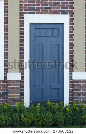 green bushes in front of entrance wooden door in an old brick wall - stock photo