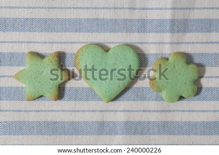 Green butter cookies, heart, flower and star shaped, on a striped fabric napkin