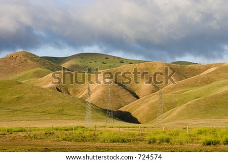 Green California hills with power lines and towers in the mid ground.