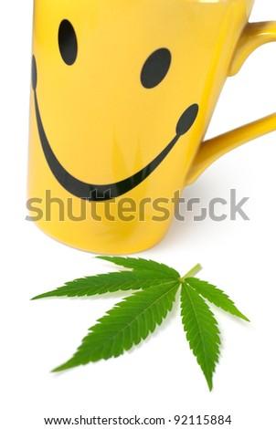 Green Cannabis (Marijuana) leaf next to yellow cup of tea on white background - stock photo