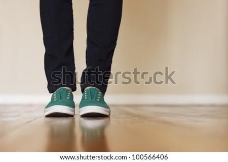 Green canvas sneakers standing on wooden floor. - stock photo