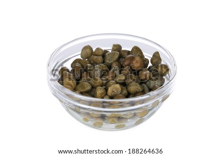 Green capers in a glass bowl. Isolated on a white background. - stock photo