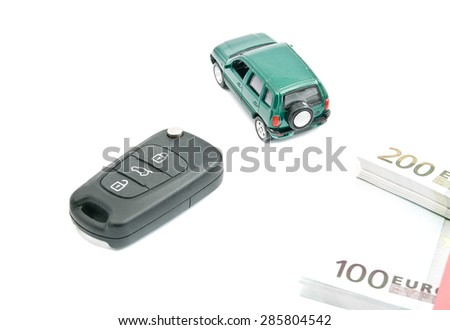Green car, black car keys and euro notes on white - stock photo