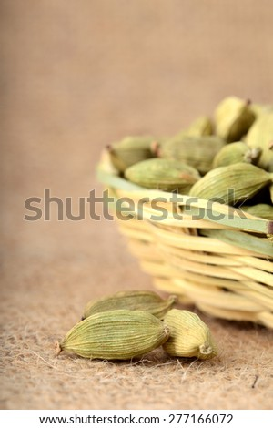 Green Cardamom pods in bamboo basket on sack cloth  - stock photo