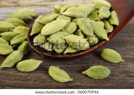 green cardamom pods  in wooden spoon - stock photo