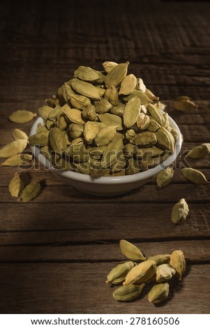 Green cardamom seeds against wooden background - stock photo