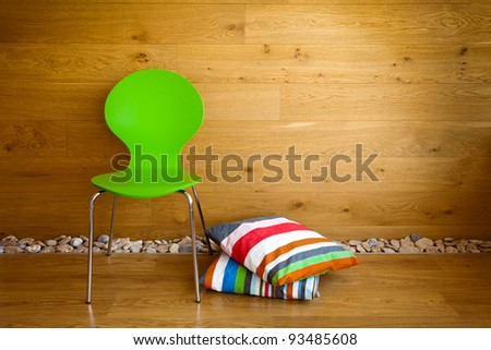 Green Chair and colorful pillows against wooden wall / Modern interior - stock photo