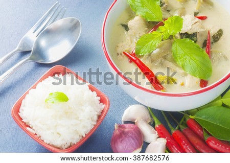 Green chicken curry with raw spicy ingredient and rice with spoon and fork, Thai traditional food - stock photo