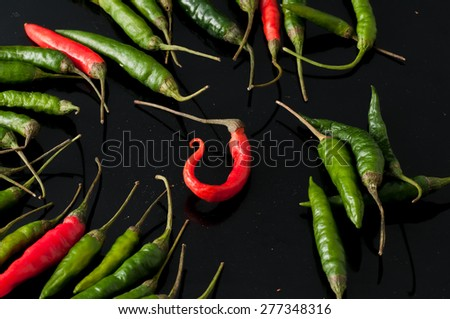 green chili peppers and red on a black background - stock photo