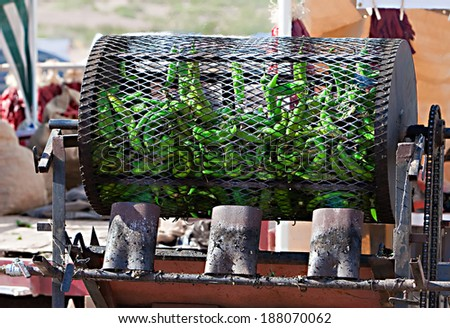 Green chilis are fire roasted in a large metal drum - stock photo