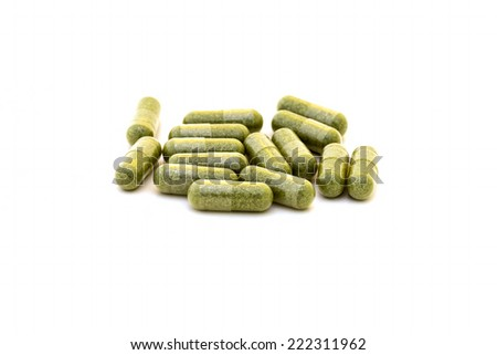 Green chlorophyll capsules on white background  - stock photo