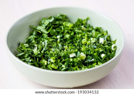 Green chopped herbs in bowl, parsley, ramson, spring onion - stock photo
