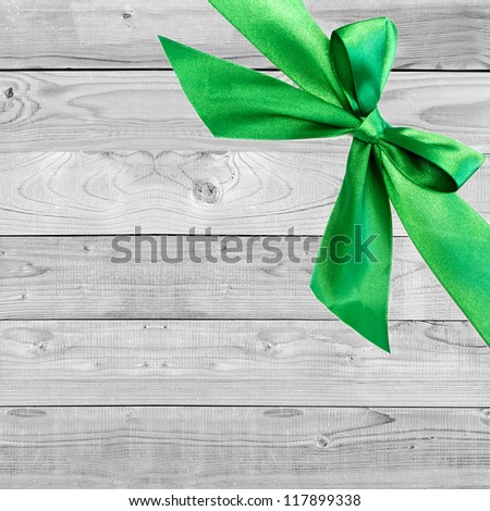 green Christmas bow on grunge wooden grey  background with space for text