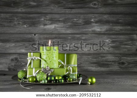 Green christmas decoration with candle and presents on wooden grey background. - stock photo