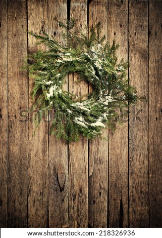 Green Christmas Natural Fir Tree Wreath with Snow on Branches on Wooden Background, vertical image and vignette effect - stock photo