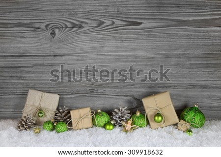 Green Christmas presents wrapped in natural paper on old wooden grey background. - stock photo
