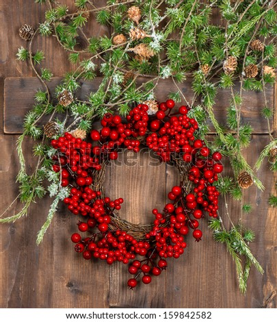 green christmas tree branches and wreath from red berries over rustic wooden background. bright festive decoration