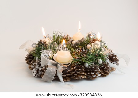 green Christmas wreath decorated with cones candles and bows