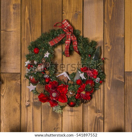 Green Christmas Wreath with Red, White, Brown Decorations on Wooden Planks Background.