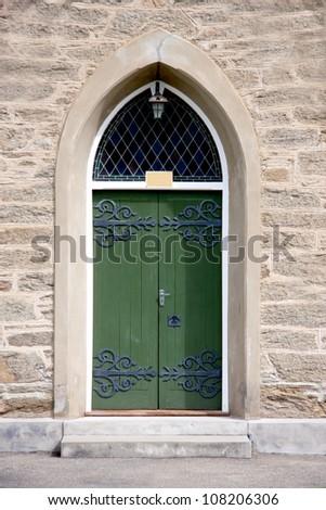 Green church door on sandstone church - stock photo