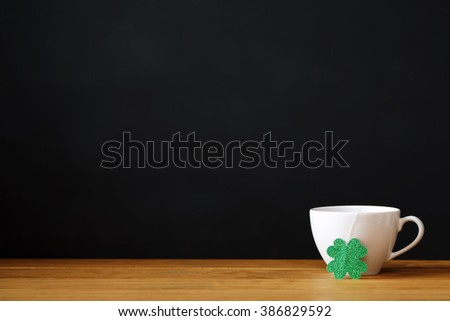 Green clover with white coffee cup on black background - stock photo