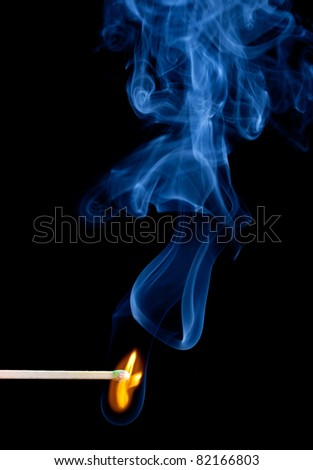 Green coated match head starts to burn with light blue smoke - stock photo