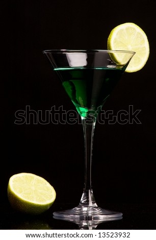 Green cocktail with green lemon on black background - stock photo