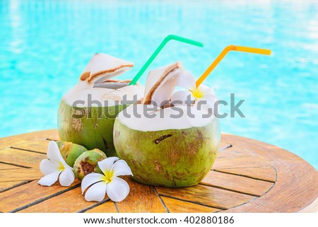 Green coconuts and flower on wood table at swimming pool in summer. - stock photo