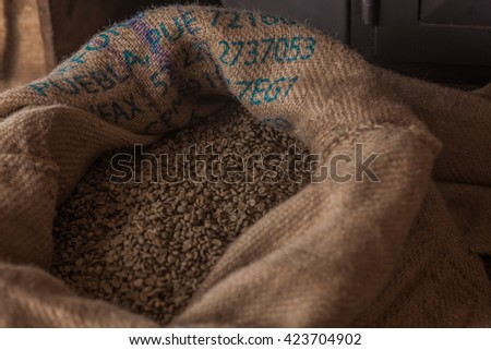 green coffee beans in a canvas sack - stock photo