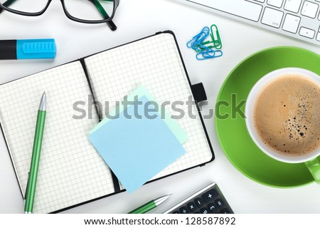 Green coffee cup and office supplies. View from above. Closeup